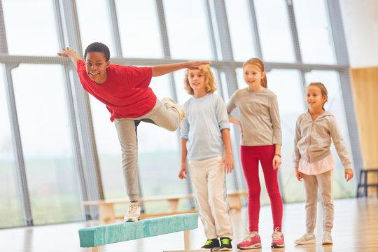 Children on balance beam train coordination