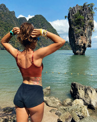 Beautiful young woman posing against the backdrop of James Bond Island in Phang Nga Province of Thailand, the most popular place in Phuket for travel, sightseeing and tourist tours
