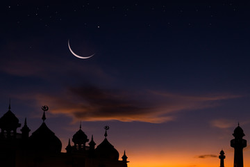 mosque at sunset and crescent moon over silhouette mosque