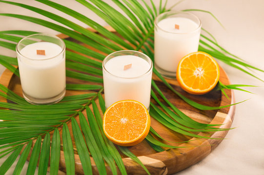 White candles and oranges on a wooden tray with palm leaf