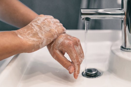 Hand washing personal hygiene woman washing hands rubbing soap for 20 seconds following steps, cleaning wrists and rinsing under water at home bathroom. COVID-19 infection prevention handwashing.