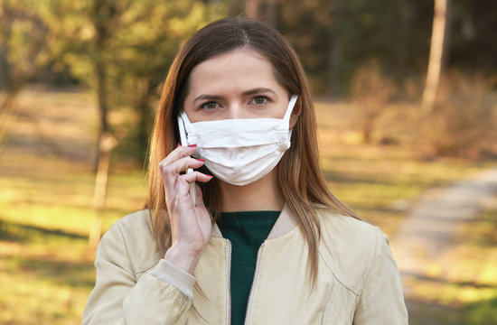 Young woman with white cotton hand made face nose mouth mask talking over her mobile phone while walking in park, close portrait. Can be used during coronavirus covid-19 outbreak prevention