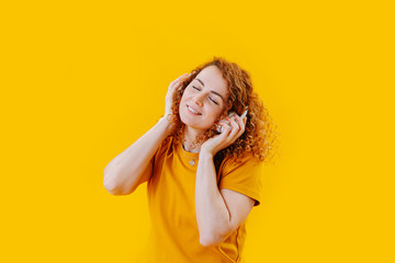 Smiling woman with curly red hair immersed in music over yellow