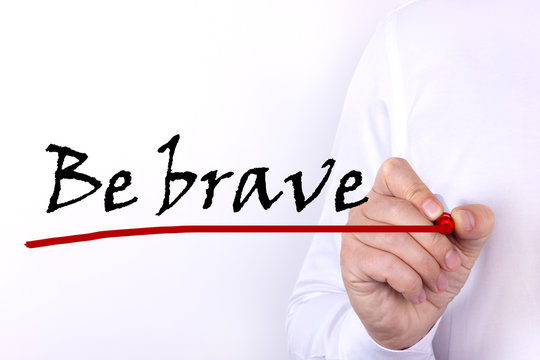 A person writes text, a word, the phrase Be Brave with marker on a light background. Business concept.