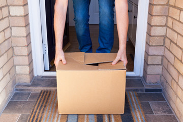 Person receiving a home delivery at a front doorstep