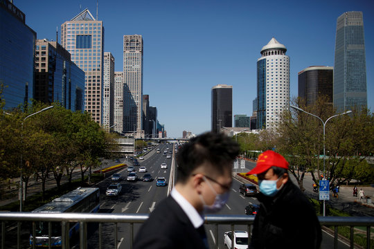 "People wearing protective masks cross a bridge in the Central Business District on a ""blue sky day"" in Beijing as the spread of the novel coronavirus disease (COVID-19) continues"
