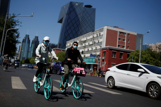 "People wearing protective masks ride bikes in the Central Business District on a ""blue sky day"" in Beijing as the spread of the novel coronavirus disease (COVID-19) continues"