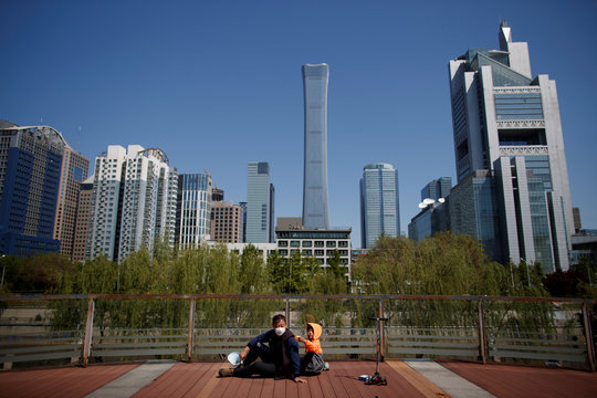"A man and a child sit in a park near the Central Business District on a ""blue sky day"" in Beijing as the spread of the novel coronavirus disease (COVID-19) continues"