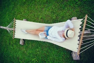 Fototapeta hamak, dziewczyna, kapelusz, relaks, czyta, książka, mazury,  obraz