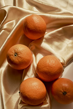 Many oranges on a bright yellow satin texture.