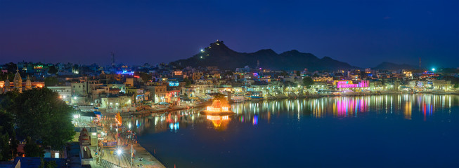 Wall Mural - View of famous indian hinduism pilgrimage town sacred holy hindu religious city Pushkar with Brahma temple, aarti ceremony, lake and ghats illuminated at sunset. Rajasthan, India. Horizontal pan