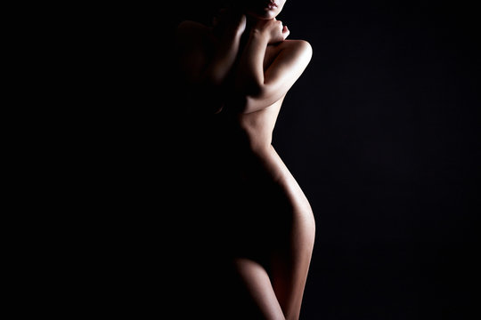 Nude Woman silhouette under light in the dark