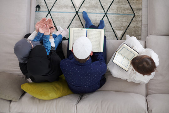 muslim family reading Quran and praying at home top view