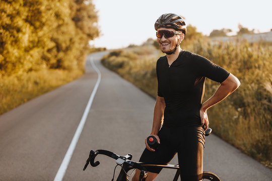 Cheerful bearded man in activewear, black helmet and sport glasses sitting on bike and looking on camera with beautiful nature around. Concept of active and healthy lifestyle.