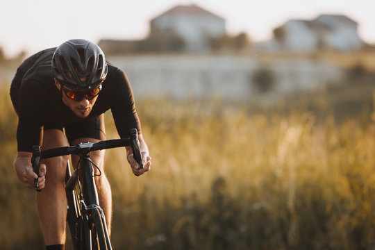 Close up of male athlete in cycling clothes, black helmet and protective glasses looks very concentrated while riding bicycle among nature countryside. Active lifestyle and sport concept
