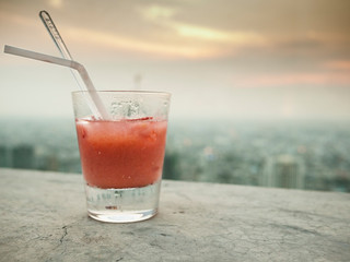 Glass Of Juice With The View Of A City In The Background