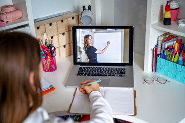 Teacher giving lesson online on video chat. Teenager girl studying at home looking at tutor at...