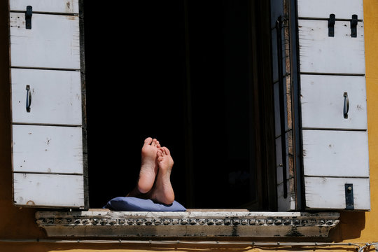Feets are seen at the window as Italy's lockdown measures continue to prevent the spread of coronavirus disease (COVID-19) in Venice