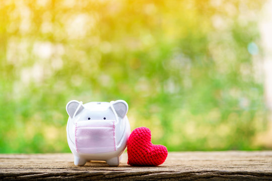 Sick piggy bank wearing surgical mask to prevent viruses and diseases put beside the red heart in the public park, saving money for buy health insurance for family concept.