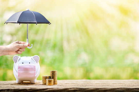 Woman hand hold the black umbrella for protect to sick piggy bank wearing surgical mask to prevent viruses and diseases put beside three stack gold, Saving money for buy health insurance concept.