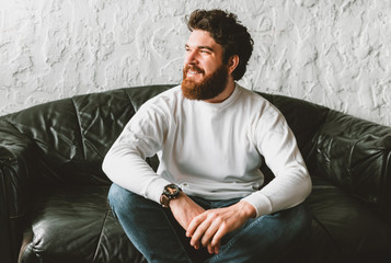 Portrait of handsome bearded man looking away and sitting on sofa Wall mural