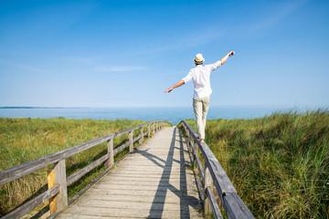 Wall Mural - Young man enjoying his freedom near the beach