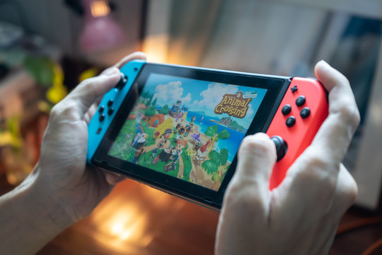 Bangkok, Thailand - March 21, 2020 : A man playing Animal Crossing, a popular game during the quarantine, on Nintendo Switch.