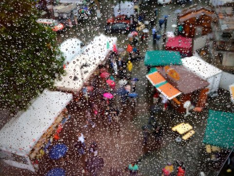 People At Market Seen From Wet Glass Window During Monsoon
