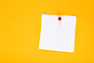 Blank white note paper pinned with a push pin on a yellow notice board
