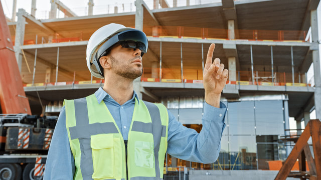 Futuristic Architectural Engineer Wearing Augmented Reality Headset and Using Gestures to Control Commercial Building Construction Site. In Background Skyscraper Formwork Frames and Industrial Crane