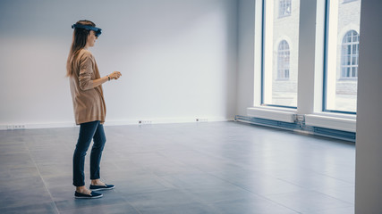 Young Hipster Woman in Holographic Augmented Reality Glasses Standing in Empty Office and Map it. Sunlight Shines Through Big Windows.