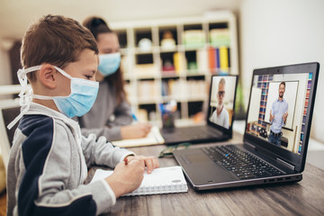 Boy and girl studies at home, wear protective masks, and doing school homework. Distance learning...