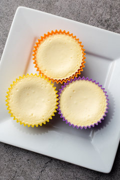 Mini cheesecakes with whipped cream topping, healthy summer treat on grey stone table