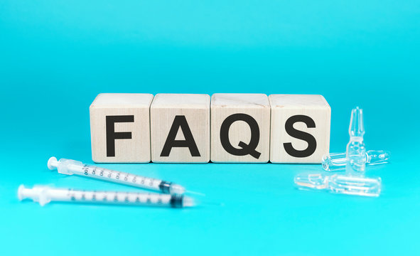 Word FAQS on wooden block. Syringe and ampoule on a blue background.