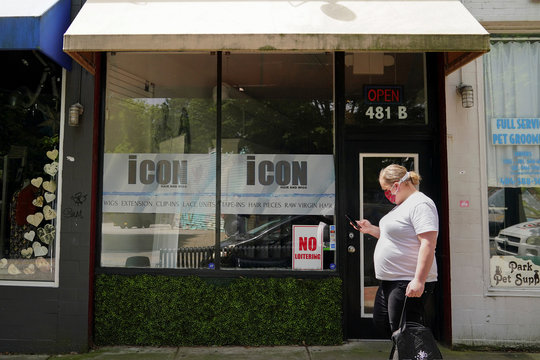 A woman carrying a Postmates delivery bag passes by a hair salon and wig shop days before the phased reopening of businesses from coronavirus disease rules in Atlanta