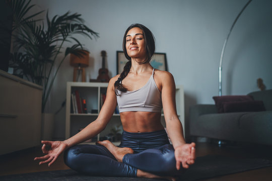 Beautiful hispanic woman practicing mindfulness yoga at home sitting on yoga mat smiling happy with closed eyes breathing fresh air enjoy peace of mind no stress free
