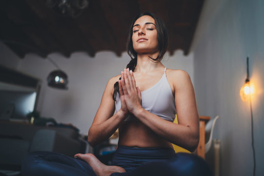 Young healthy beautiful woman in sportive top and leggings practicing yoga at home sitting in lotus pose on yoga mat meditating smiling relaxed with closed eyes, Mindfulness meditation concept