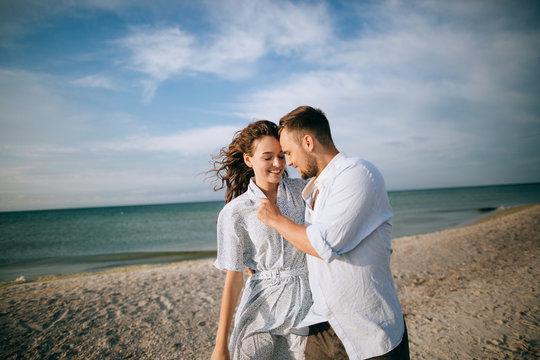 Happy man and woman smiling and hugging at sea beach. Summer holidays and vacations