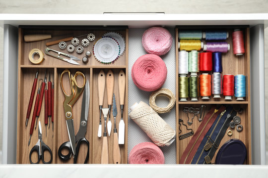 Sewing accessories in open desk drawer, top view