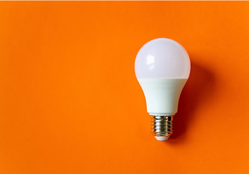 White energy saving light bulb on an orange background with copy space. LED white bulb, concept of new idea