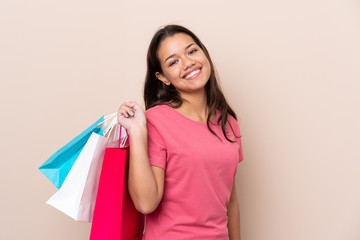 Young Colombian girl with shopping bag over isolated background holding shopping bags and smiling
