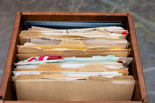 Old handwritten recipes on 3x5 index cards with tabs in wooden box