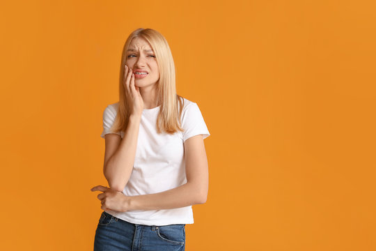 Stressed woman with dental braces on color background
