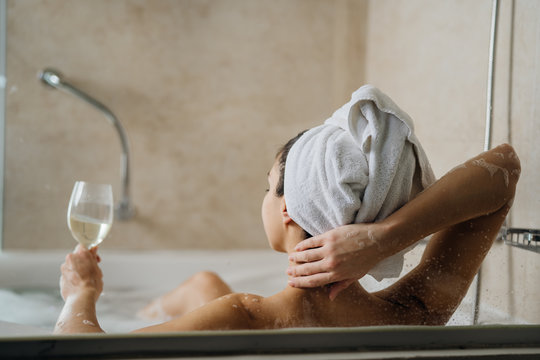 Woman relaxing at home in the hot tub bath ritual,drinking wine.Relaxing spa night in bathroom.Good personal hygiene routine.Skin,body care,aromatherapy.Bath essential oils.Stress relief after work