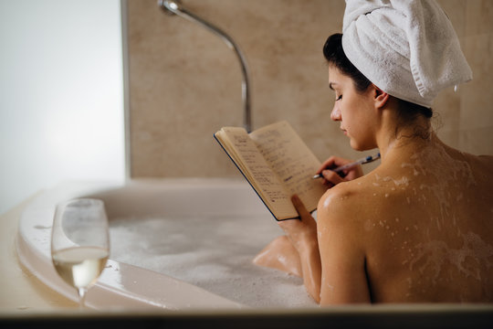Calm woman having a relaxing bath at home.Spa self care night.Inspired creative person writing gratitude diary/journal.Resolution list.Making plans.Writing thoughts and ideas.Motivation.Enjoying life