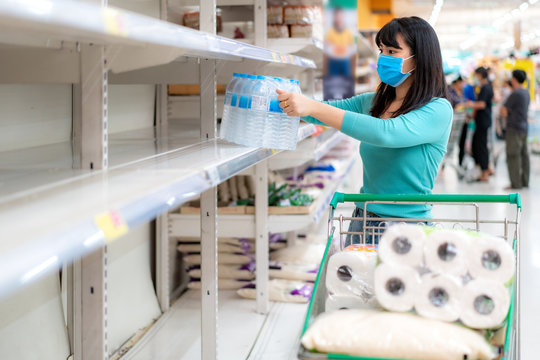 Asian woman looking at Supermarket empty drink water bottle shelves amid COVID-19 coronavirus fears, shoppers panic buying and stockpiling toilet paper preparing for a pandemic.