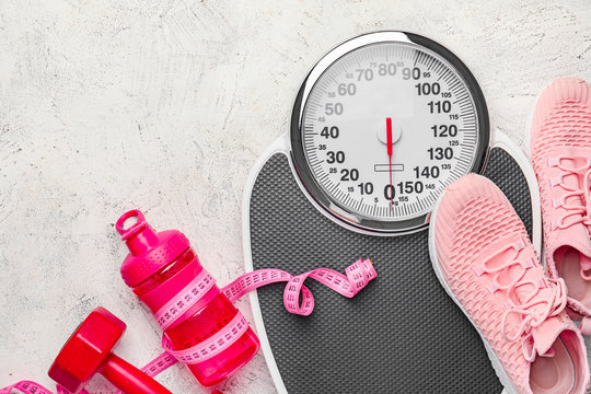 Weight scales with measuring tape, sport shoes, dumbbell and bottle of water on light background