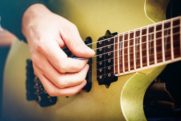 Electric Guitar Close Up With Fingers Playing It. Toned Image