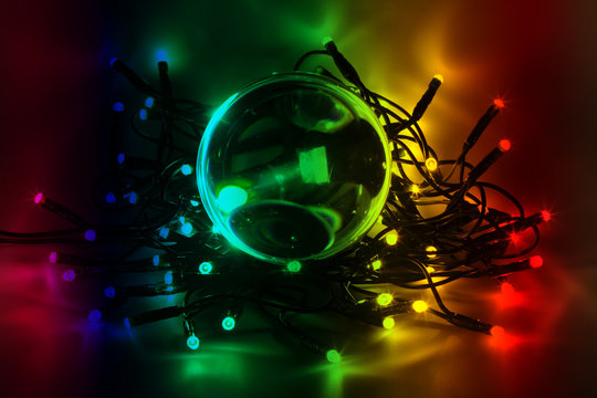 Close-up Of Illuminated Colorful Christmas Lights And Crystal Ball