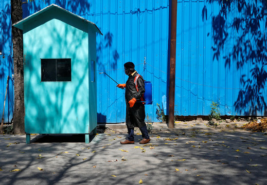Dev Dutt Sharma, a sanitation worker, disinfects a guard checkpost in a residential colony, during an extended nationwide lockdown to slow the spread of the coronavirus disease (COVID-19), in New Delhi
